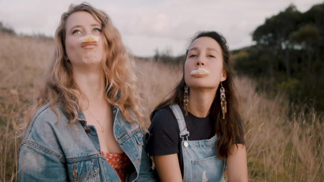 stockvideo's en b-roll-footage met playful young women eating oranges together at picnic outside - dranken en maaltijden