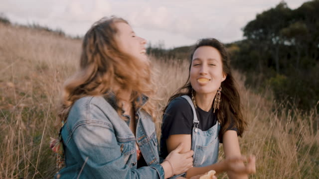 playful young women eating oranges together at picnic outside - picnic stock-videos und b-roll-filmmaterial