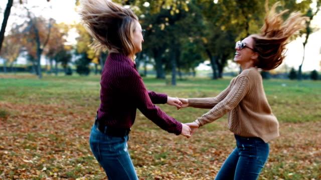 vidéos et rushes de ludiques jeunes femmes tenant les mains et spining - tournoyer