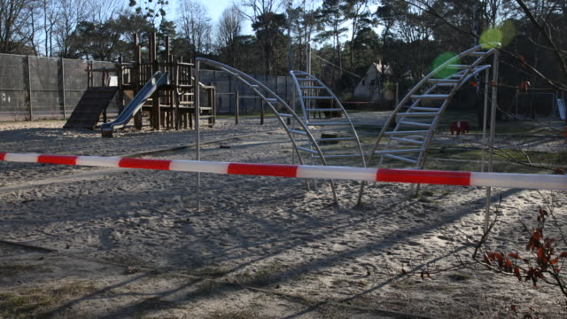 playground in berlin-zehlendorf, which is closed with barrier tape following the tightening of measures affecting public life due to the coronavirus... - tape measure video stock e b–roll