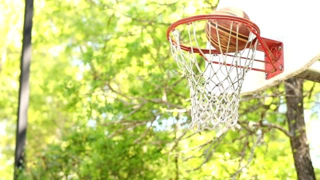 vidéos et rushes de jouer au basket sur le terrain de parc en plein air en été, au printemps. - streetball