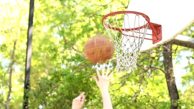 vidéos et rushes de jouer au basket-ball sur la cour extérieure de parc en été, printemps. - streetball
