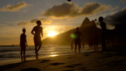 Playing beach football at sunset on Ipanema Beach, Brazil