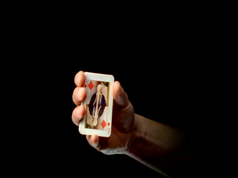 Playing card pops out from deck in mans hand