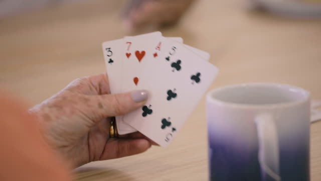 playing cards - a woman lowers her poker hand into frame - hand of cards stock videos & royalty-free footage
