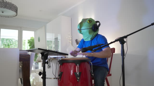 playing congas and goofing around during a video call wearing a lizard mask - reptile stock videos & royalty-free footage