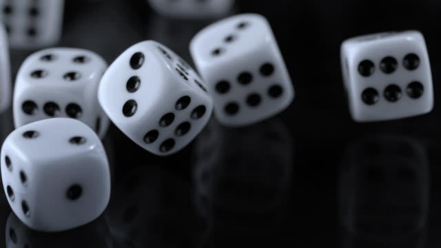 slo mo playing dice rolling around on a black surface - dice stock videos & royalty-free footage