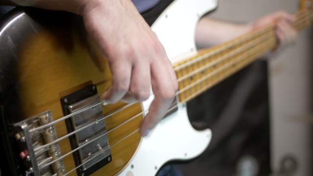 Playing electric bass close up