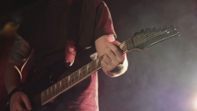 vídeos de stock, filmes e b-roll de playing electric guitar on stage during gig - guitarist