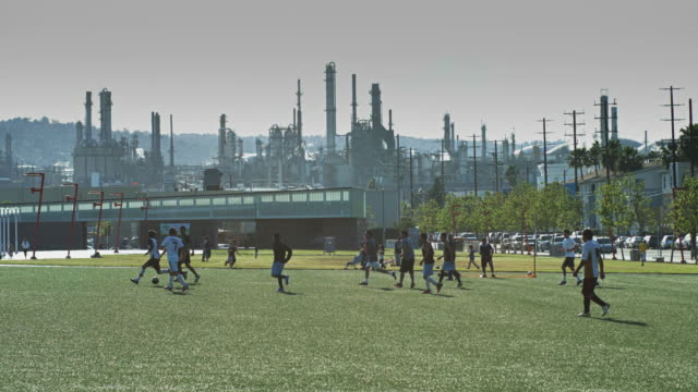 playing football by oil refinery - refinery stock videos & royalty-free footage