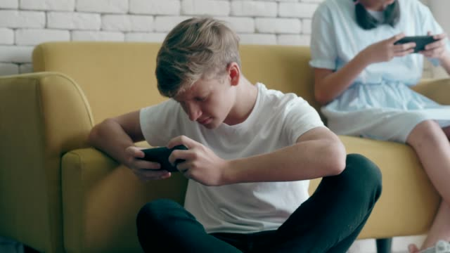 playing game in smartphone - teenage boys stock videos & royalty-free footage