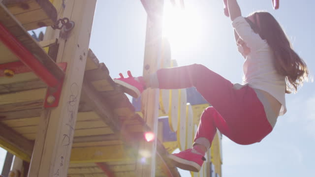 playing girl on playground with sun flairs - 40 o più secondi video stock e b–roll