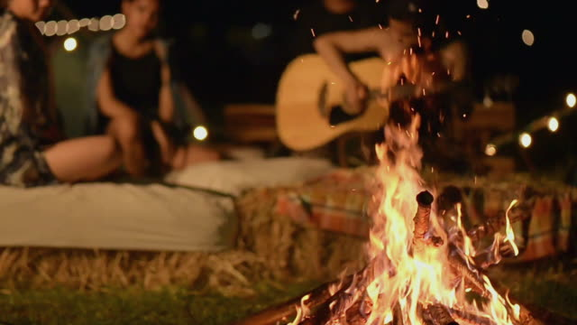 playing guitar and singing at campfire site - guitar stock videos & royalty-free footage
