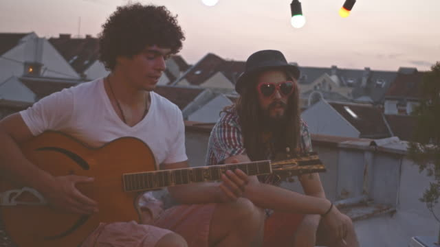 playing guitar with friend on rooftop party - roof stock videos and b-roll footage
