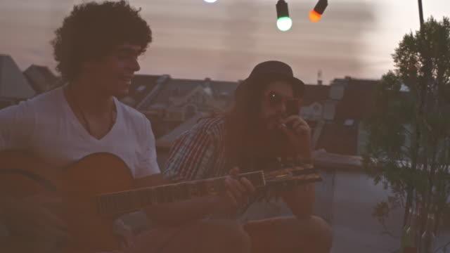 屋上パーティーで友人とギターを弾く - ギタリスト点の映像素材/bロール