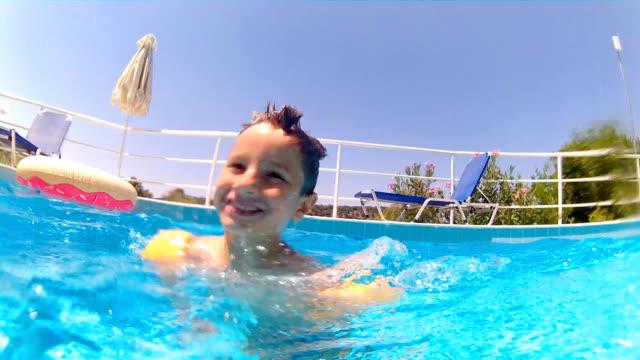 spielen im swimmingpool - schwimmflügel stock-videos und b-roll-filmmaterial