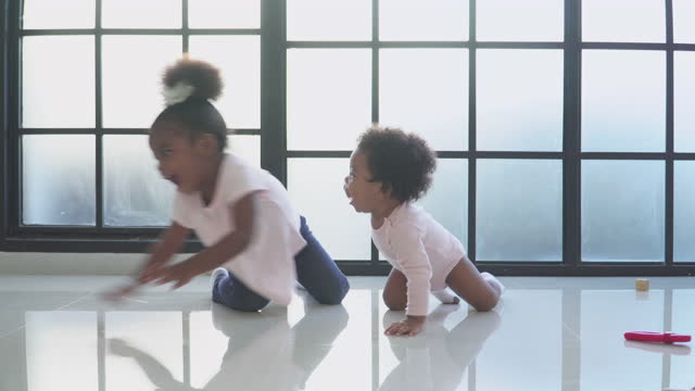 playing of sibling, african daughter crawling to play with a little sister in the living room, concept of preschool, childhood - 2 3 years stock videos & royalty-free footage