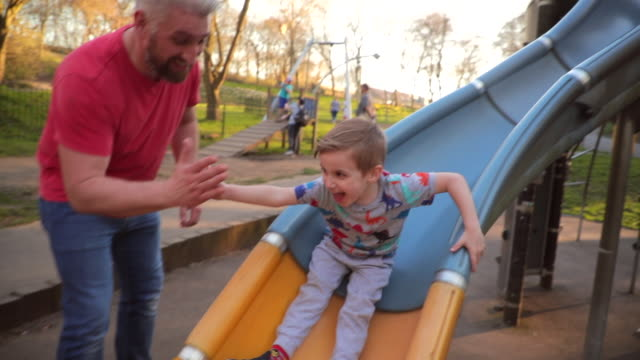 playing on the slide in the park - parco giochi video stock e b–roll