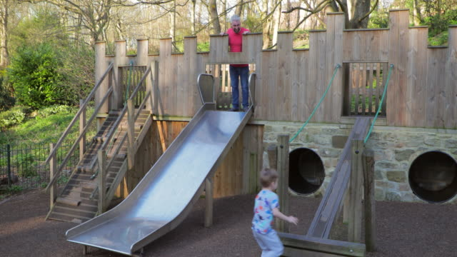playing on the slide in the park - jungle gym stock videos and b-roll footage