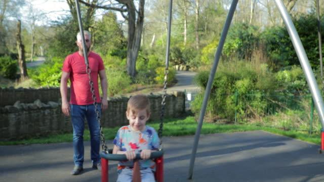 spielen auf der schaukel im park - schaukel stock-videos und b-roll-filmmaterial