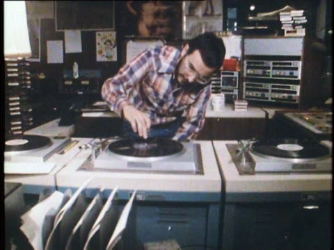 stockvideo's en b-roll-footage met 1982 dj playing records in radio studio, nyc, ny - draaitafel