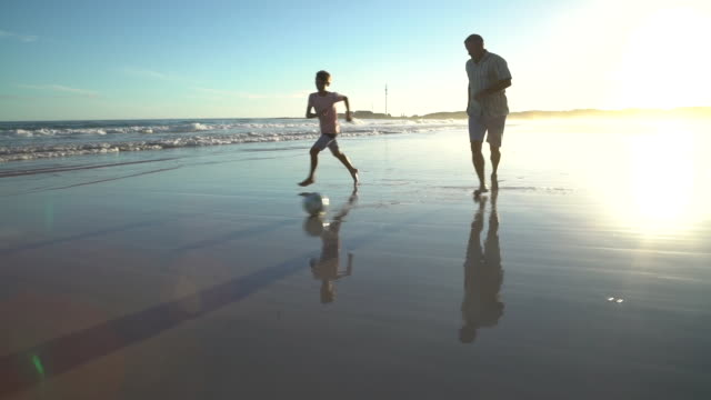 playing soccer on a beach at sunset - 50 54 years stock videos & royalty-free footage