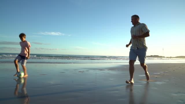 vídeos de stock, filmes e b-roll de playing soccer on a beach at sunset - son