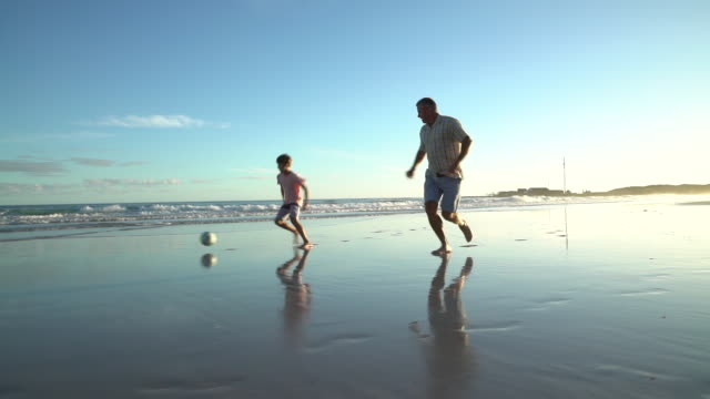 vídeos de stock e filmes b-roll de playing soccer on a beach at sunset - homens adultos