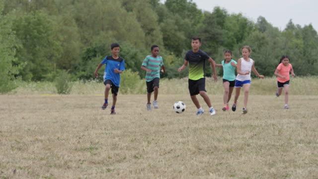 fußball spielen mit freunden im sommer - 6 7 jahre stock-videos und b-roll-filmmaterial