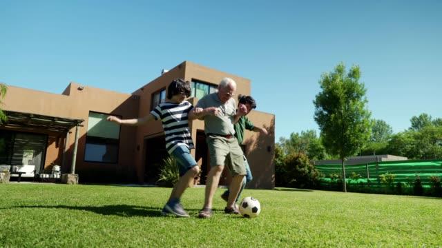 fußball spielen mit opa - drei personen stock-videos und b-roll-filmmaterial