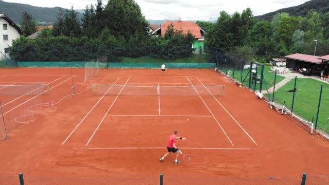 vidéos et rushes de jouer au tennis est amusant - terrain de sport sur gazon