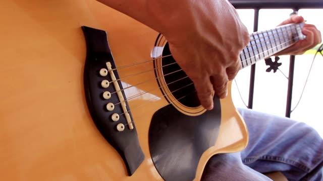 vídeos de stock, filmes e b-roll de tocando guitarra acústica - violão acústico