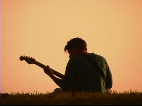 playing the guitar - 若い男性だけ点の映像素材/bロール