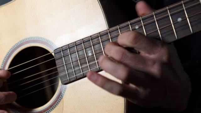 vídeos de stock e filmes b-roll de playing the perfect chord, a musician playing the guitar, music, entertainment, outdoors, close-up shot, enjoying the music, fun, zen-like, rhythm - cultura latino americana