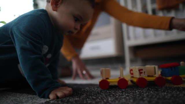 giocare con il suo giocattolo preferito in una stanza di cura - tirare video stock e b–roll