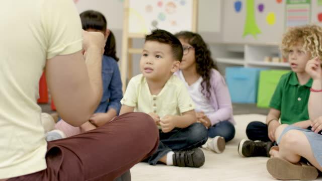 gemeinsam spielen im kindergarten mit männlichem lehrer - vorschulalter stock-videos und b-roll-filmmaterial