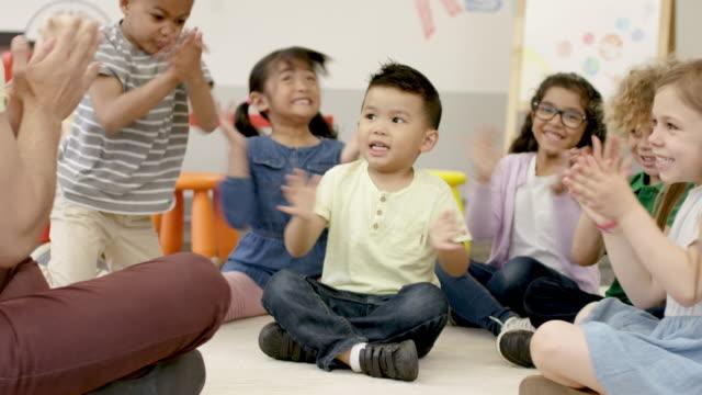 vídeos y material grabado en eventos de stock de jugando juntos en preescolar con el maestro masculino - escuela preescolar