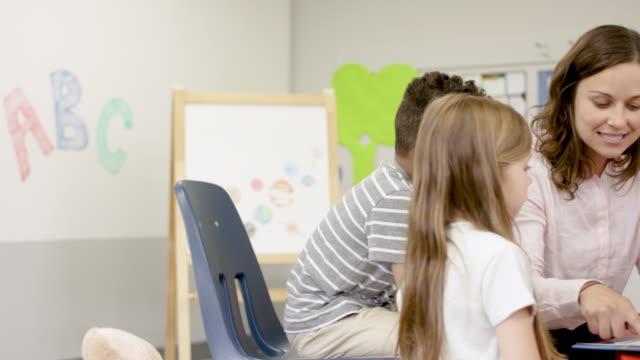 vídeos y material grabado en eventos de stock de jugando juntos en preescolar con el maestro masculino - niño pre escolar