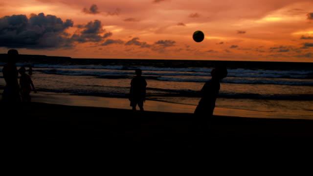 vídeos de stock, filmes e b-roll de ws brincando com bola na praia de kuta - raw footage