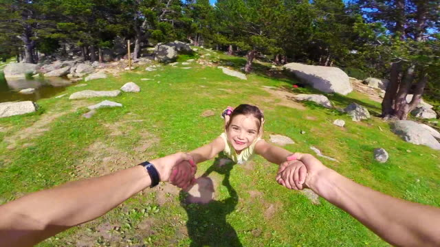 vídeos de stock e filmes b-roll de playing with little girl spinning around holding hands recorded from personal perspective near the lake in the catalan pyrenees on summer. - segurar