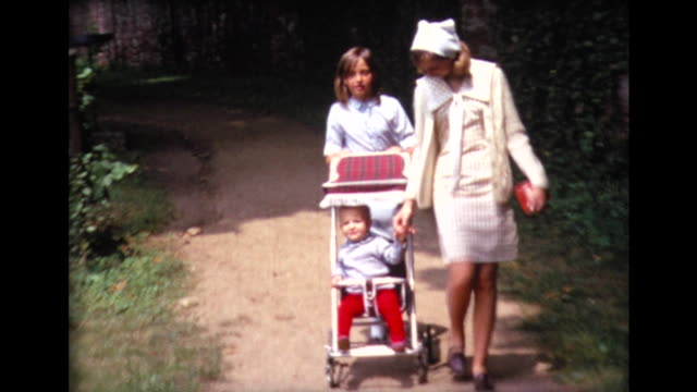 1967 playing with toddler in a stroller