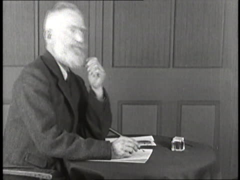 playwright george bernard shaw sits at a table thinking and writing. - 脚本家点の映像素材/bロール