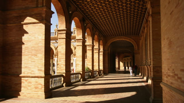 ms, t/l, plaza de espana, people walking in arched  corridor in palacio espanol, seville, andalucia, spain - 20世紀のスタイル点の映像素材/bロール
