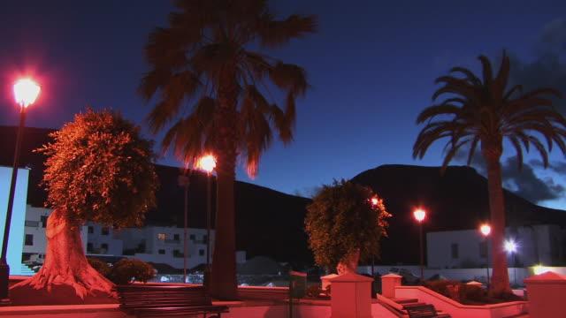 vídeos de stock e filmes b-roll de ms, plaza de los remedios at dusk, yaiza, lanzarote, canary islands, spain - fan palm tree