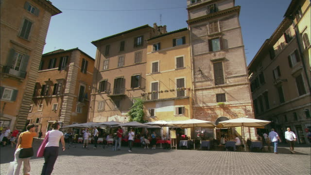 ws plaza in rome bustling with pedestrians and surrounded by old apartment houses / rome, lazio, italy - appartamento video stock e b–roll