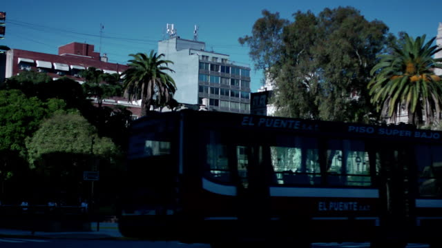 plaza, vehicles driving, unidentifiable people in silhouette walking, palm trees, city buildings, argentine national justice palace courthouse,... - plaza de la república buenos aires stock videos & royalty-free footage