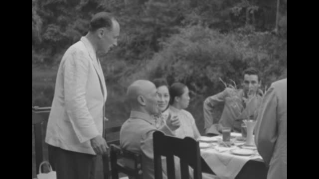 vídeos y material grabado en eventos de stock de pleasant garden party with round tables / journalist arthur menken stands at table and chats with chiang kaishek and his wife madame chiang / note... - chiang kai shek