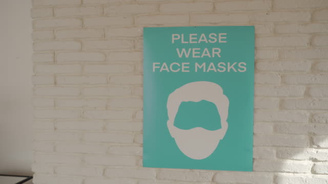 please wear face mask sign on wall in in empty modern office - poster stock videos & royalty-free footage
