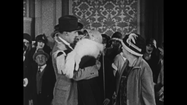 vidéos et rushes de 1924 pleased woman kisses man and then sits with him on sofa - 1924