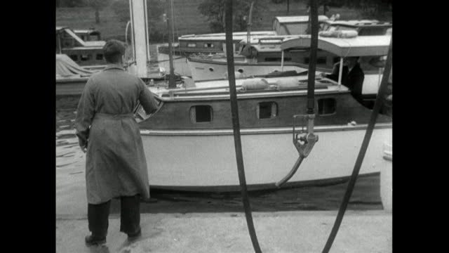 pleasure boat is refuelled at a riverbank fuel pump; 1950 - riverbank stock videos & royalty-free footage